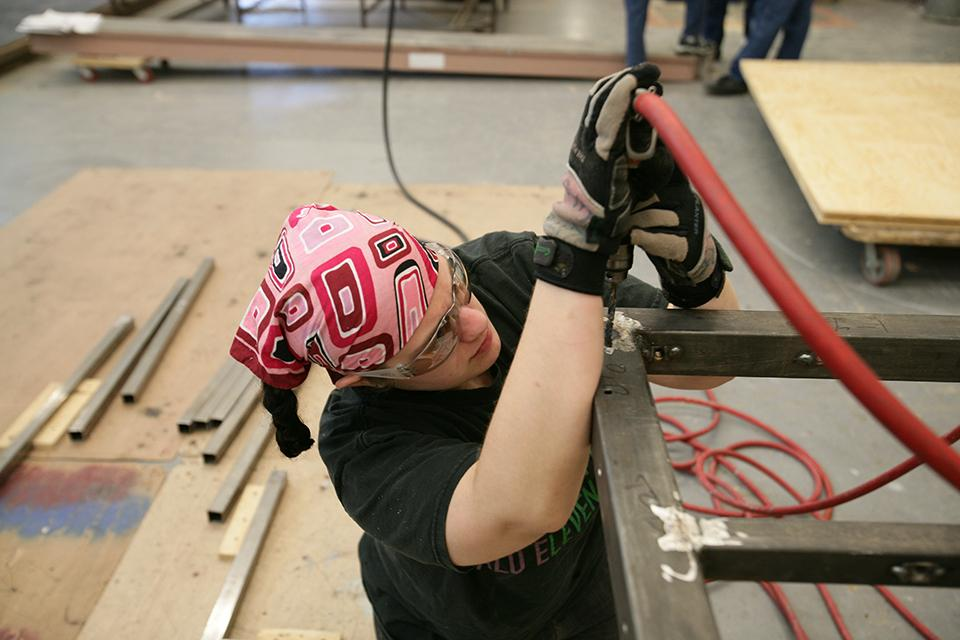 "A student works in the scenic technology shop to prepare pieces for ""West Side Story."""