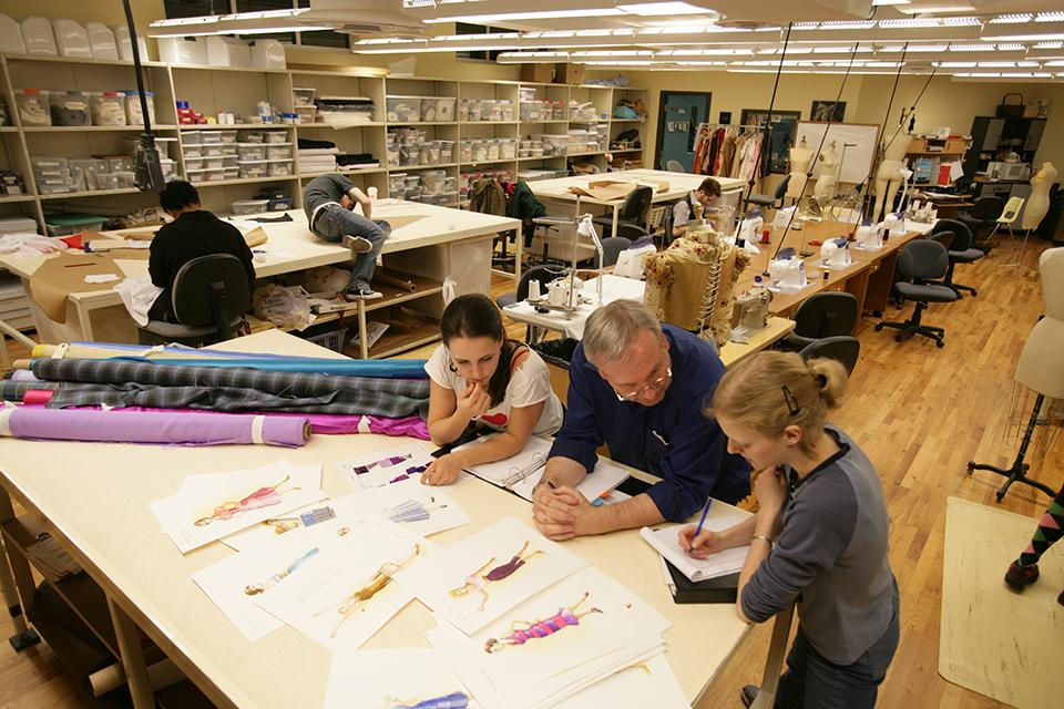 Students in the costume shop review designs with a faculty member.