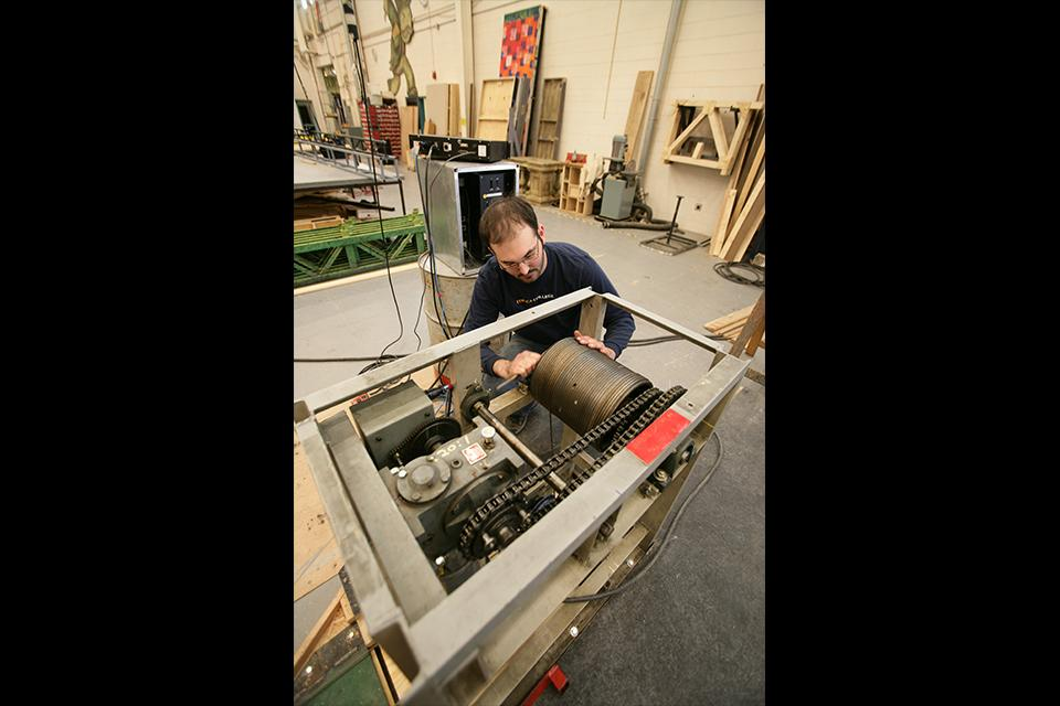 "A scenic technology student works in the shop on ""West Side Story."""