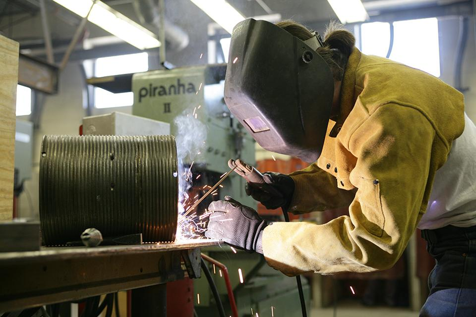 """A student welds a piece that will be used on stage in """"West Side Story."""""""