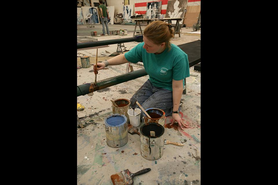 """A student works on the paint deck, preparing an aged piece of pipe for """"West Side Story."""""""