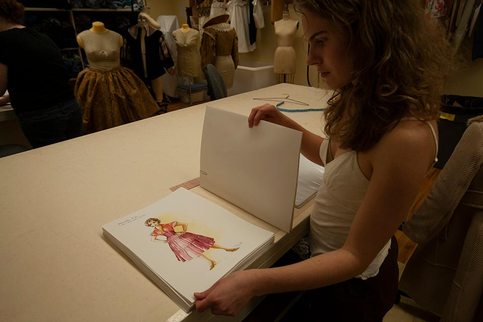 "A student reviews costume designs for Anita in ""West Side Story."""