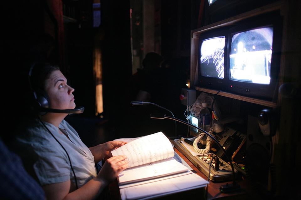 A stage manager closely watches the monitors backstage at the Stevens Center.
