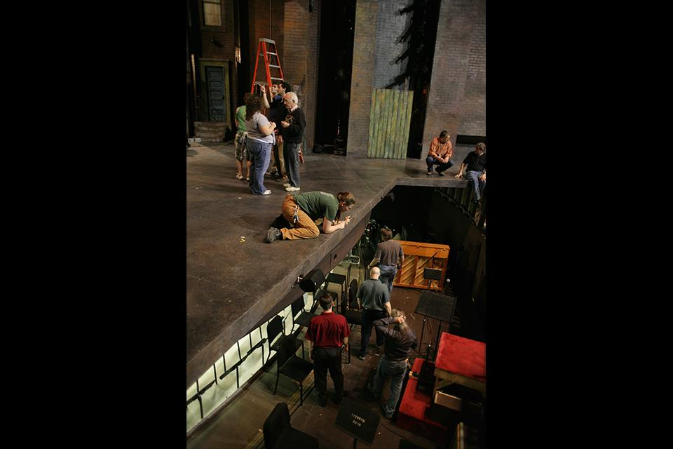 Students prepare the pit and the stage for rehearsals in the Stevens Center.