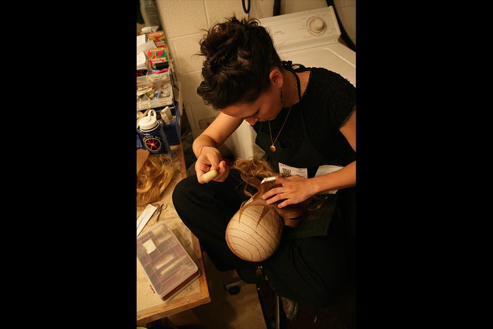 A student prepares a wig backstage.