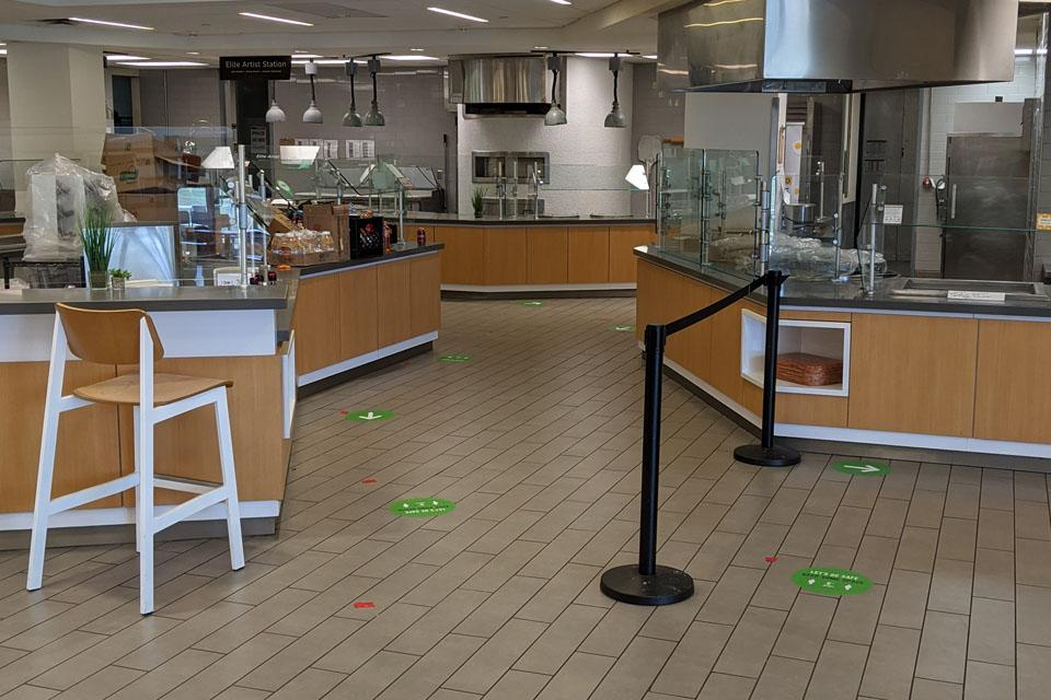 Directional signage and barriers to help guide people in the Dining Hall.