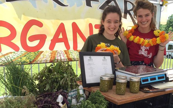 Hannah Myers (right) helps sell produce from Ryder Farm at the local farmer's market.
