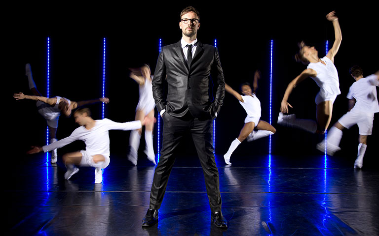 Trey McIntyre on stage in a suit with dancers