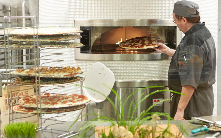Man putting pizza in oven