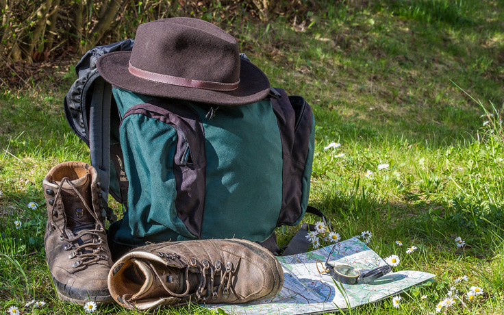Hiking boots, backpack and map