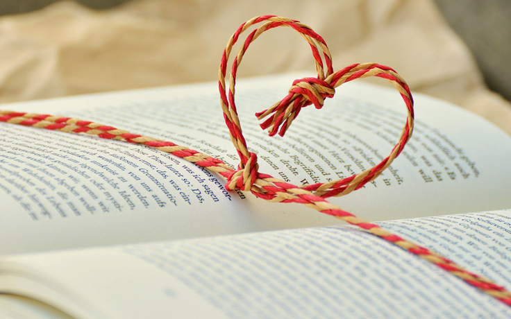 Open book with a string tied into a heart