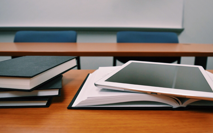 Books, tablet on desk in a classroom
