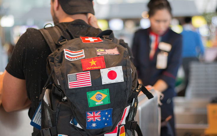 Man wearing backpack with international flags