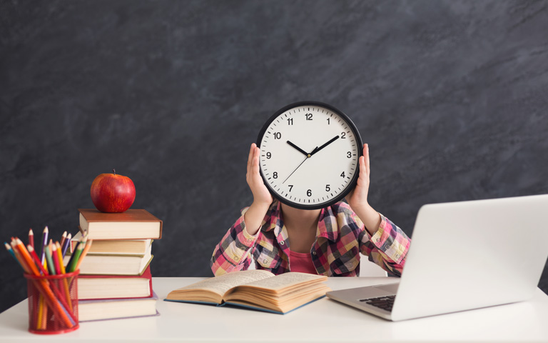 Student with clock in front of face