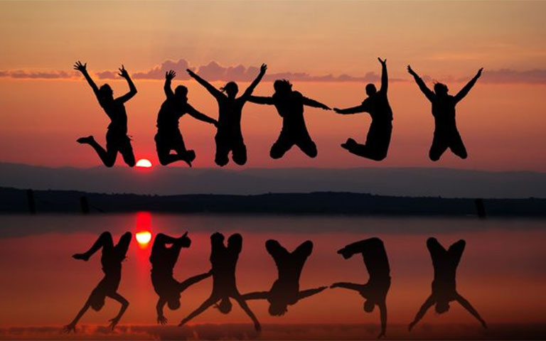 Group of people jumping at sunset