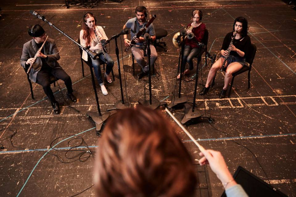 A graduate student in Film Music Composition conducts musicians performing her score for a student film