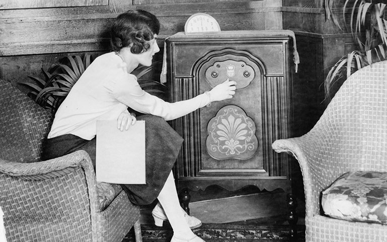 Woman tuning a radio in the 1920s
